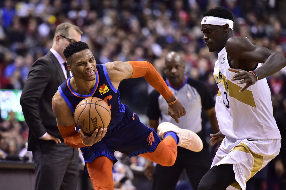 Photo - Oklahoma City Thunder guard Russell Westbrook, left, and Toronto Raptors forward Pascal Siakam (43) battle during second-half NBA basketball game action in Toronto, Friday, March 22, 2019. (Frank Gunn/The Canadian Press via AP)