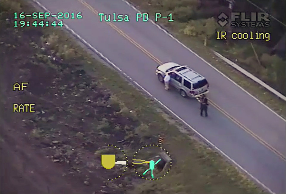 Photo -  In this photo made from a Sept. 16, 2016 police video, Terence Crutcher, left, lowers his right arm as he is pursued by police officers moments before he was shot and killed by one of the officers in Tulsa. [Tulsa Police Department via AP]