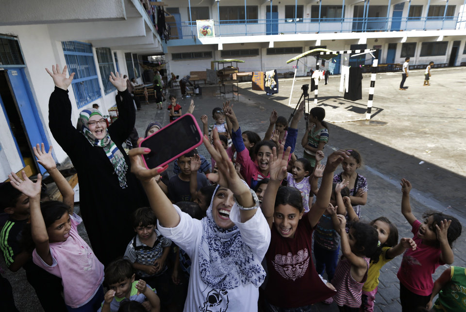 Photo - Volunteer Nisreen Shawa, 25, centre, uses her mobile phone to take a 'selfie' photo as she leads a play session with displaced Palestinian children at a U.N. school where they had sought refuge along with their families during the war, in Gaza City, Gaza Strip, Thursday, Aug. 7, 2014. Taking advantage of the continuing ceasefire, volunteers from the local non-profit NGO 'Tomooh' (Ambition), arranged a special play session for children to try and lessen the stress they've been enduring after the weeks of conflict. In the playground the children got a chance to sing and play group games under the caring eye of volunteers. They hope that their efforts will lessen the damage of the traumatic recent weeks events, or at least help them forget for a short while. (AP Photo/Lefteris Pitarakis)