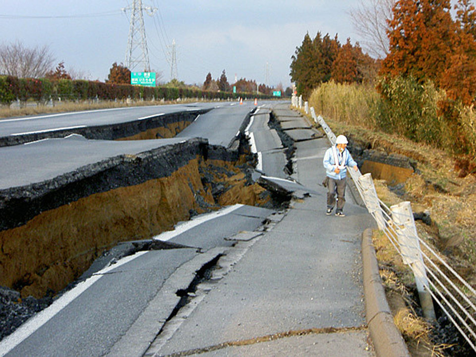 Photo - In this photo released by Nexco East Japan, a worker inspects a caved-in section of the Joban Motorway near Mito, Ibaraki Prefecture, after one of the largest earthquakes ever recorded in Japan slammed its eastern coast Friday, March 11, 2011. (AP Photo/Nexco East Japan via kyodo News) JAPAN OUT, MANDATORY CREDIT, NO SALES ORG XMIT: TOK849