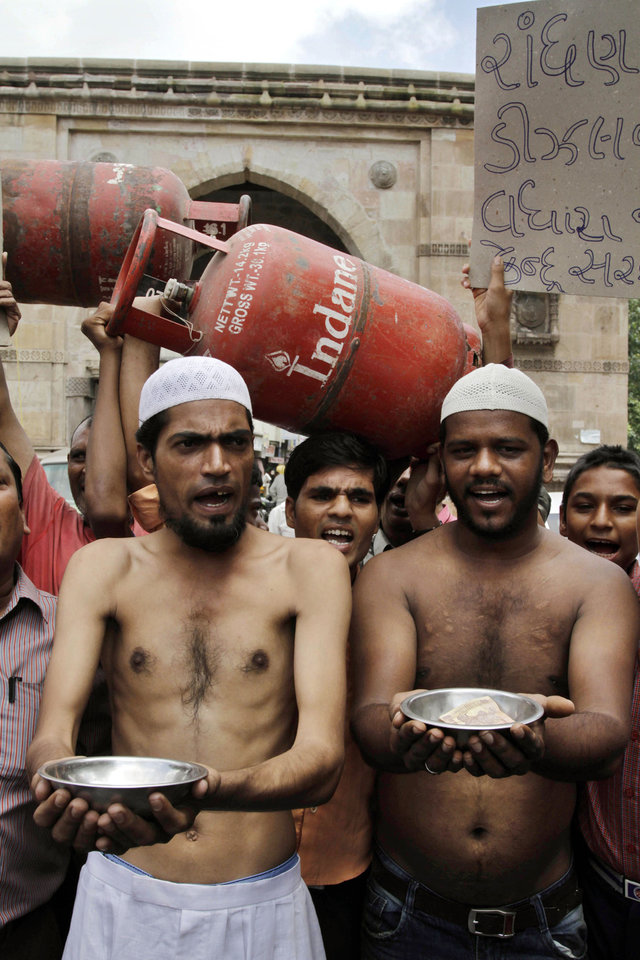 Photo -   Indian Muslim men act like beggars to collect alms during a protest against the price hike in diesel and capping the number of subsidized cooking gas cylinders in Ahmadabad, India, Friday, Sept. 14, 2012. India's government is facing angry protests from its political allies as well as the opposition after it raised the price of diesel fuel in a bid to curb its ballooning fiscal deficit and also announced a reduction in cooking gas subsidies. (AP Photo/Ajit Solanki)