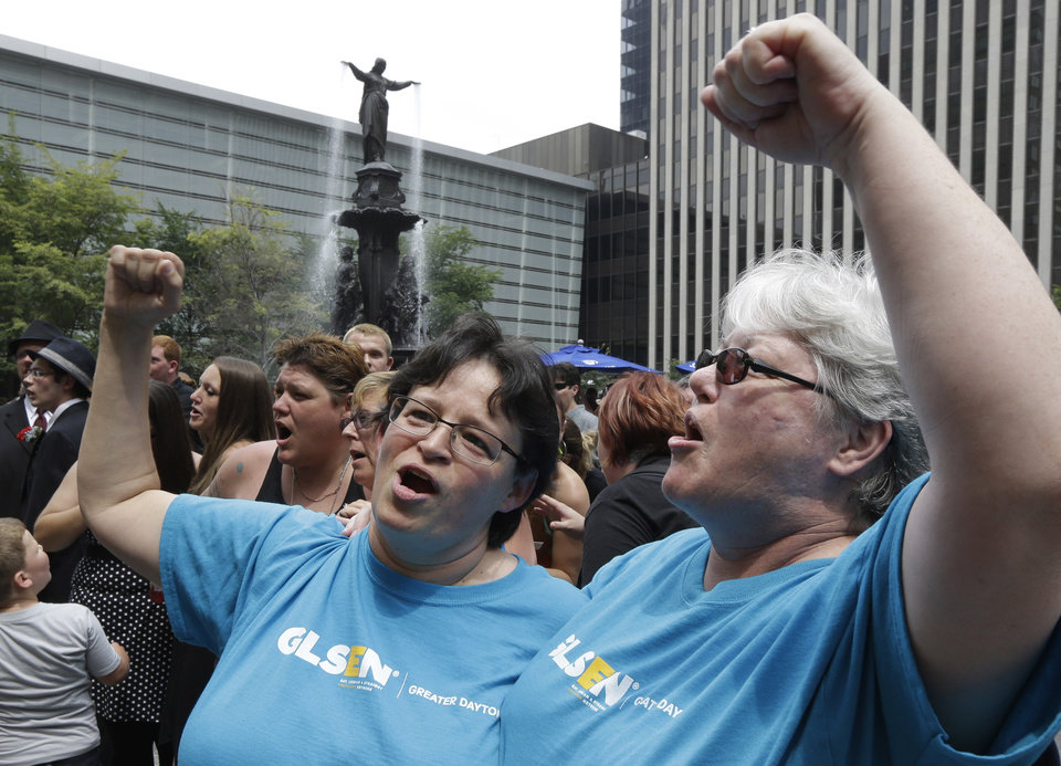 Photo - Tina Gilley, left, and Skye McKenna cheer after they were united in a commitment ceremony, Wednesday, Aug. 6, 2014, on Fountain Square in Cincinnati. Three judges of the 6th U.S. Circuit Court of Appeals in Cincinnati are set to hear arguments Wednesday in six gay marriage fights from four states, Kentucky, Michigan, Ohio and Tennessee. (AP Photo/Al Behrman)