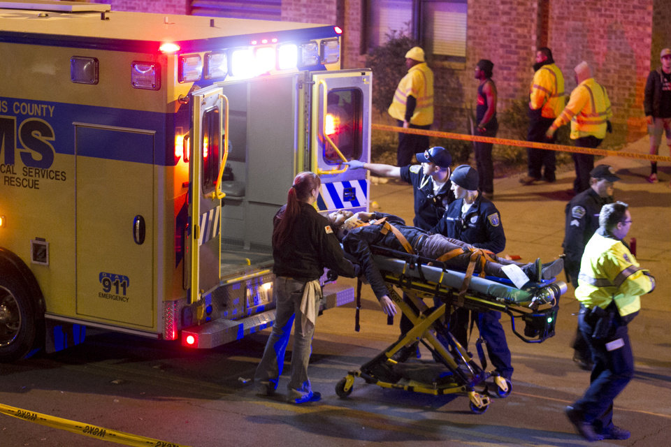 Photo - A man is transported to an ambulance after being struck by a vehicle on Red River Street in downtown Austin, Texas, during SXSW on Wednesday March 12, 2014. Police say two people were confirmed dead at the scene after a car drove through temporary barricades set up for the South By Southwest festival and struck a crowd of pedestrians.  (AP Photo/Austin American-Statesman, Jay Janner)