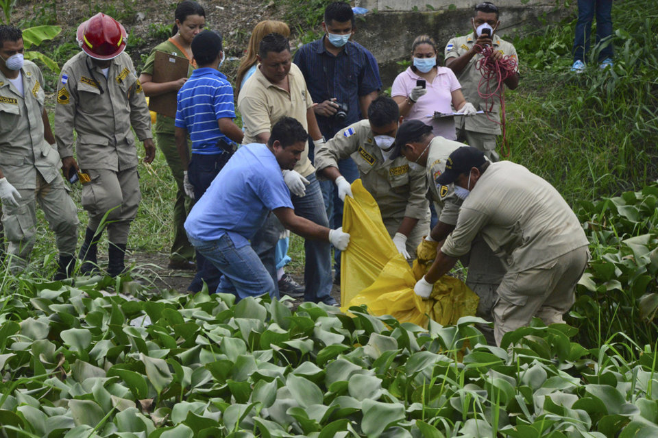 Photo - CORRECTS DATE - Firefighters remove a body found in a field on the outskirts of San Pedro Sula, Honduras, Tuesday, July 9, 2013. Honduran authorities have confirmed that the charred and mutilated body found here is that of missing journalist Anibal Barrow. The 62-year-old journalist had a popular daily morning news show called