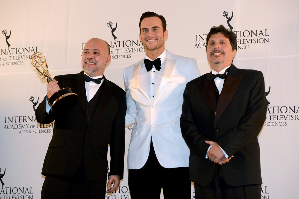 Photo -   Brazilians Claudio Torres, left, and Mauro Wilson, right, flank presenter Cheyenne Jackson after winning the Comedy award for