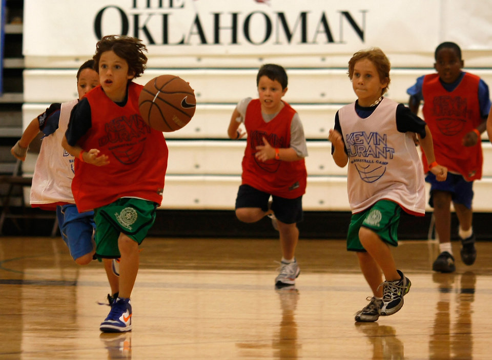Photo - Luke Chansolme (8) breaks away with the ball during the Kevin Durant Basketball Camp. Kevin Durant held a basketball camp Wednesday, June 30, 2010, at Heritage Hall in Oklahoma City. Photo by Mitchell Alcala, The Oklahoman.
