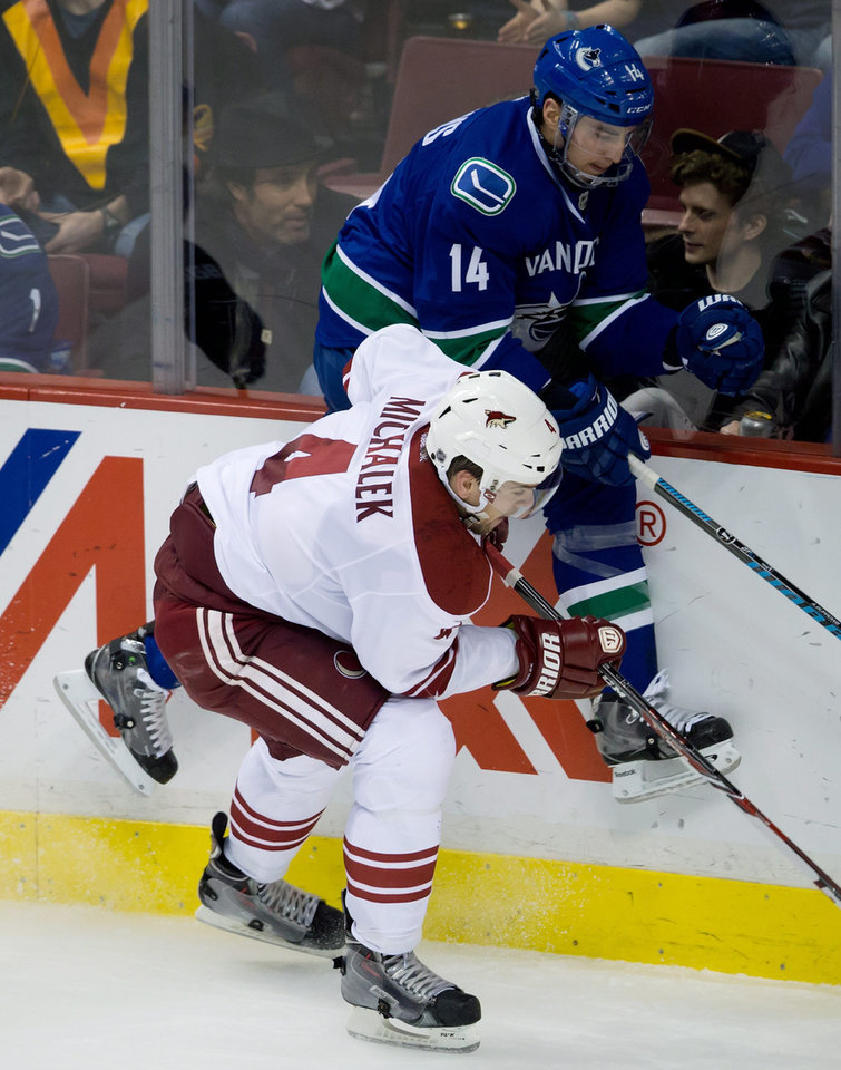 Photo - Vancouver Canucks' Alex Burrows, right, and Phoenix Coyotes' Zbynek Michalek, of the Czech Republic, collide during the second period of an NHL hockey game in Vancouver, British Columbia, on Sunday, Jan. 26, 2014. (AP Photo/The Canadian Press, Darryl Dyck)
