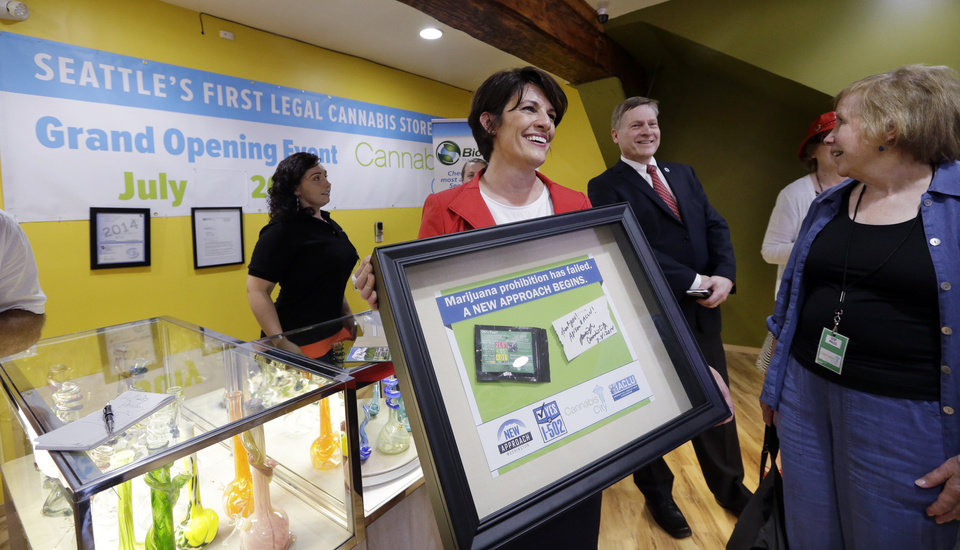 Photo - Alison Holcomb, left, criminal justice director at the Washington state ACLU, holds her framed first-purchase of legal marijuana as she stands with Seattle City Attorney Pete Holmes and state Sen. Jeanne Kohl- Welles at Cannabis City Tuesday, July 8, 2014, in Seattle, on the first day that sales of recreational pot became legal in the state. Washington on Tuesday became the second state to allow people to buy marijuana legally in the U.S. without a doctor's note as eager customers who lined up outside stores made their purchases and savored the moment. (AP Photo/Elaine Thompson, Pool)