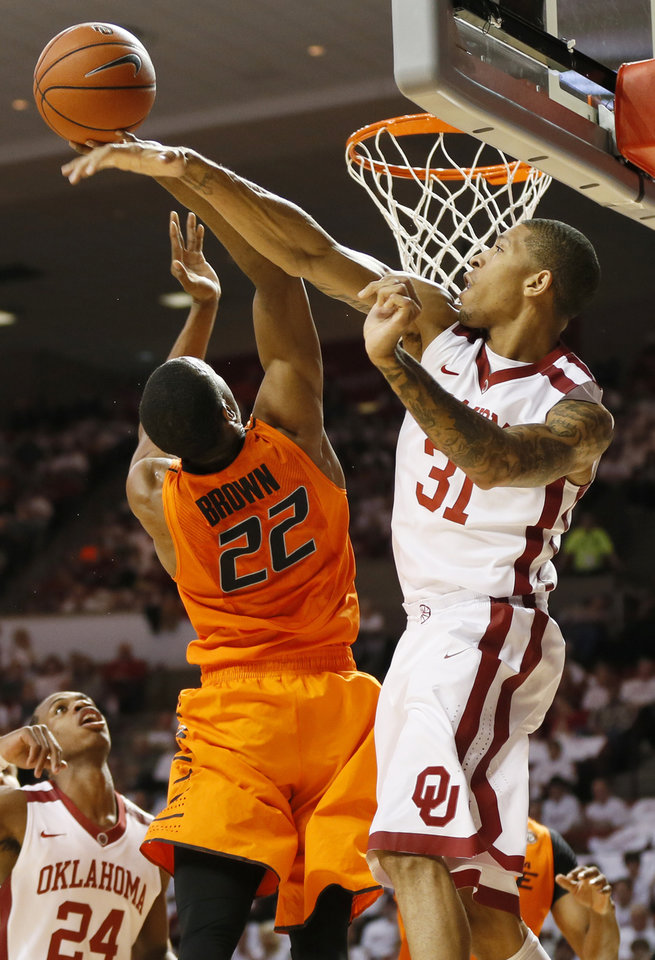 Photo - Oklahoma's D.J. Bennett (31) blocks the shot of Oklahoma State's Markel Brown (22) in the first half during the NCAA men's Bedlam basketball game between the Oklahoma State Cowboys (OSU) and the Oklahoma Sooners (OU) at Lloyd Noble Center in Norman, Okla., Monday, Jan. 27, 2014. Photo by Nate Billings, The Oklahoman