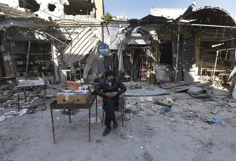 Photo - A Syrian street vendor who sells cigarette boxes, sits in front of destroyed shops which were damaged by the shelling of the Syrian forces, at Maarat al-Nuaman town, in Idlib province, Syria, Tuesday Feb. 26, 2013. Syrian rebels battled government troops near a landmark 12th century mosque in the northern city of Aleppo on Tuesday, while fierce clashes raged around a police academy west of the city, activists said. (AP Photo/Hussein Malla)