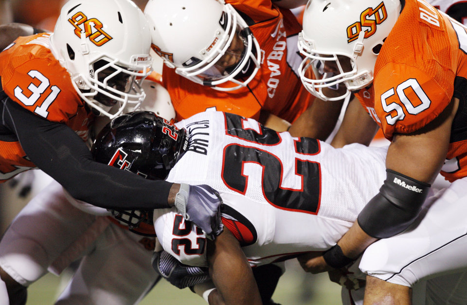 Photo - From left, OSU's Lucien Antoine, Patrick Lavine and Jamie Blatnick stop Texas Tech's Baron Batch on a carry during the college football game between Oklahoma State University (OSU) and Texas Tech University at Boone Pickens Stadium in Stillwater, Okla. Saturday, Nov. 14, 2009. Photo by Nate Billings, The Oklahoman