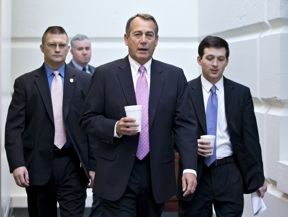 Photo - House Speaker John Boehner of Ohio, walks to a strategy session with GOP members, on Capitol Hill in Washington, Friday, Jan. 4, 2013, at the start of the first full day of business for the new 113th Congress. The House plans to hold it's first vote on a Superstorm Sandy aid package today after delays prompted GOP recriminations against the leadership. (AP Photo/J. Scott Applewhite)