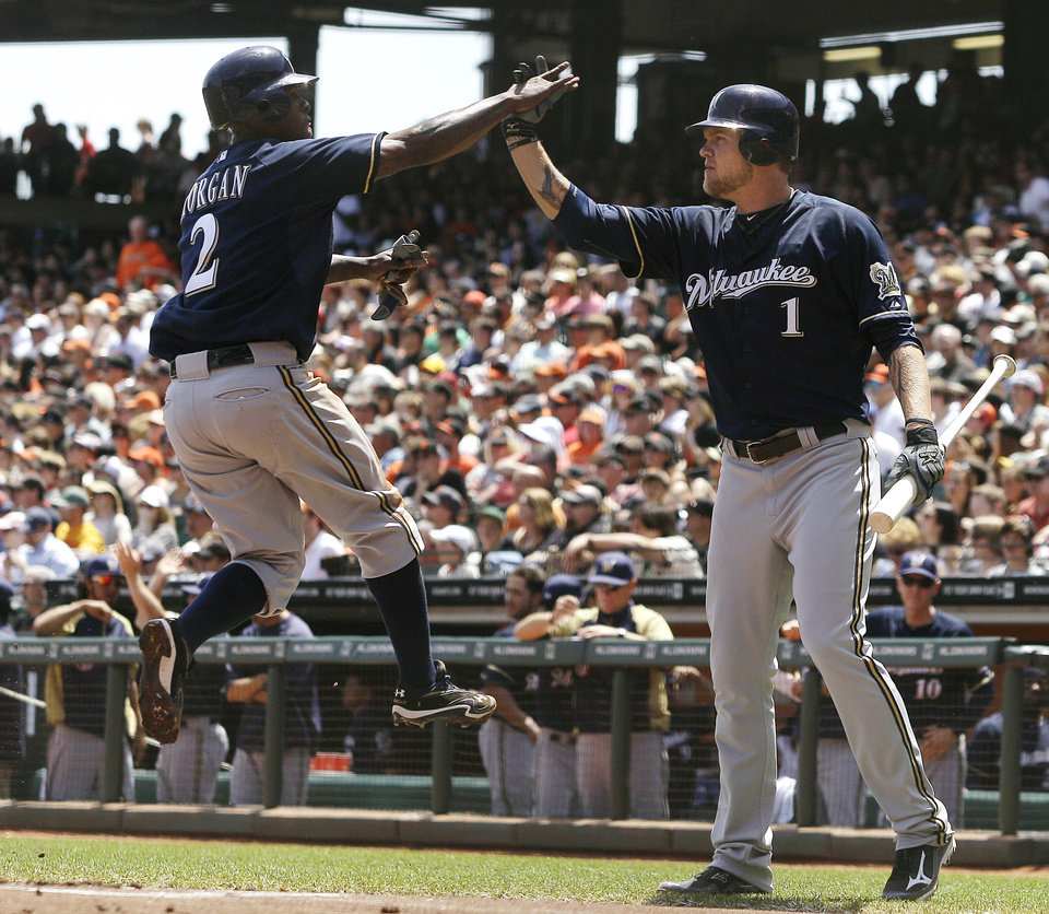 Photo -   Milwaukee Brewers' Nyjer Morgan (2) is congratulated by Corey Hart (1) after scoring on Aramis Ramirez' single off San Francisco Giants pitcher Matt Cain during the first inning of a baseball game in San Francisco, Sunday, May 6, 2012. (AP Photo/Jeff Chiu)