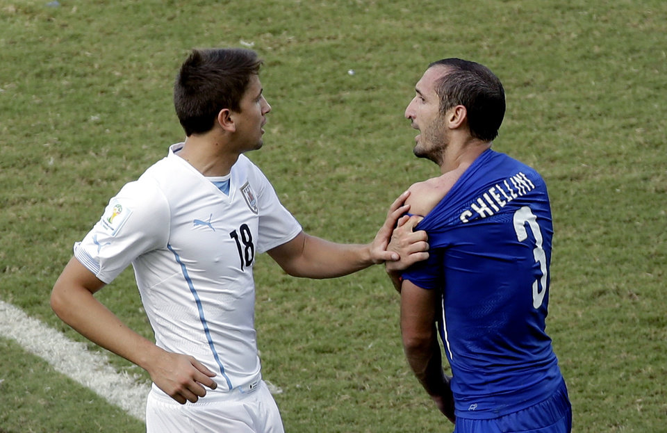 Photo - Italy's Giorgio Chiellini (3) complains after Uruguay's Luis Suarez ran into his shoulder with his teeth during the group D World Cup soccer match between Italy and Uruguay at the Arena das Dunas in Natal, Brazil, Tuesday, June 24, 2014. (AP Photo/Hassan Ammar)