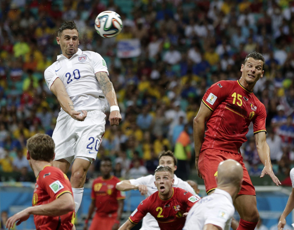 United States' Geoff Cameron heads the ball at the Belgium goal past Belgium's Daniel Van Buyten during the World Cup round of 16 soccer match between Belgium and the USA at the Arena Fonte Nova in Salvador, Brazil, Tuesday, July 1, 2014. (AP Photo/Marcio Jose Sanchez)
