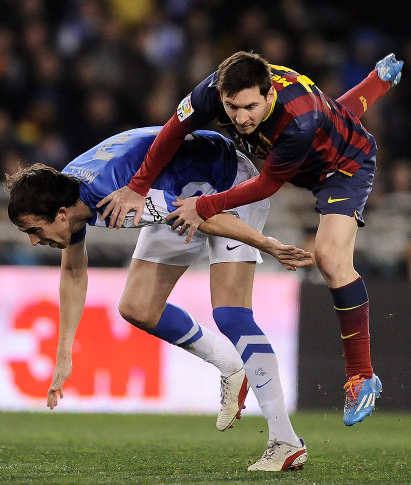 Photo - FC Barcelona's Lionel Messi of Argentina, right, clashes with Real Sociedad's Mikel Gonzalez, during their Spanish Copa del Rey semifinal second leg soccer match, at Anoeta stadium, in San Sebastian northern Spain, Wednesday, Feb. 12, 2014. (AP Photo/Alvaro Barrientos)