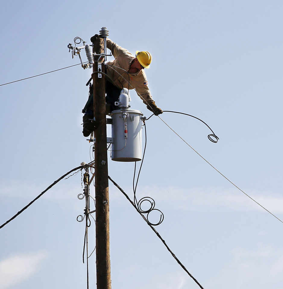 An OG&E crewman works to repair electric lines in a tornado-damaged area of Moore. PHOTO BY JIM BECKEL, THE OKLAHOMAN <strong>Jim Beckel</strong>