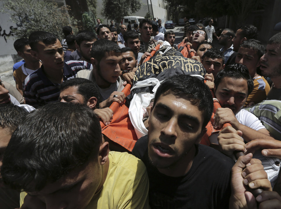 Photo - Palestinians carry the body of Islamic Jihad militant  Mohammed Sowelim, who was killed in an Israeli air strike, during his funeral in Jabaliya refugee camp, in the northern Gaza Strip, Saturday, July 12, 2014. Israeli airstrikes targeting Hamas in Gaza hit a mosque and a center for the disabled where two women were killed Saturday, raising the Palestinian death toll from the offensive to more than 120, Palestinian officials said. (AP Photo/Adel Hana)