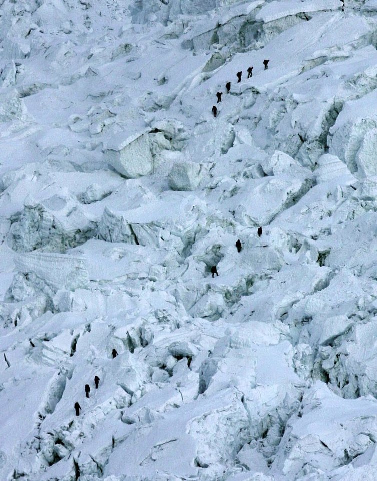 Photo - FILE - In this May 18, 2003 file photo, mountaineers pass through the treacherous Khumbu Icefall on their way to Mount Everest near Everest Base camp, Nepal. The Khumbu Icefall is a river of ice, a kilometer or so of constantly shifting glacier punctuated by deep crevasses and overhanging immensities of ice that can be as large as 10-story buildings and can move six feet in just one day. Crossing it can take 12 hours. On Friday, April 18, 2014, a piece of glacier sheared away from the mountain, setting off an avalanche of ice that killed 16 Sherpa guides as they ferried clients' equipment up the mountain. (AP Photo/Gurinder Osan, File)
