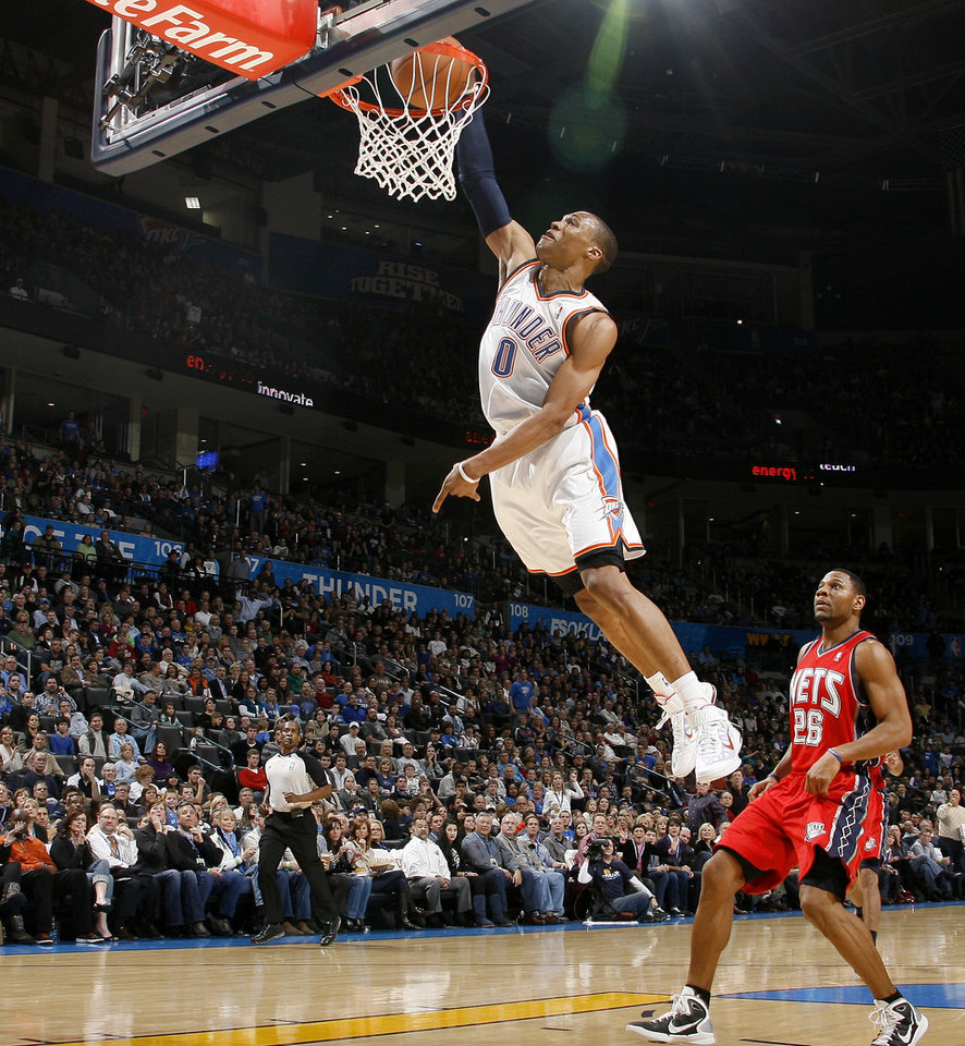 Photo - Oklahoma City's Russell Westbrook dunks the ball in front of New Jersey's Stephen Graham during the NBA basketball game between the Oklahoma City Thunder and the New Jersey Nets at the Oklahoma City Arena, Wednesday, Dec. 29, 2010.  Photo by Bryan Terry, The Oklahoman