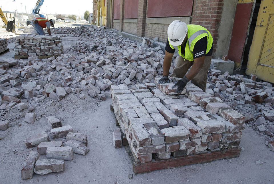 Photo - Contractors sort fallen ones from an earthquake damaged 36,000 square foot former boat shop on Mare Island, Tuesday, Aug. 26, 2014, in Vallejo, Calif. The building dates from 1904 and was used by the Navy.  The bricks are to be saved for a possible repair of the building. The historic blue-collar town of Vallejo is a short distance but a far cry from the touristy Napa Valley's vineyards and quaint towns, but when Sunday's big earthquake struck, it was not spared. The bayside city that twice was briefly the capital of California sustained more than $5 million in damage and dozens of injuries. It was the latest blow to a town that has weathered years of bankruptcy and is now beset by gangs and crime. (AP Photo/Eric Risberg)