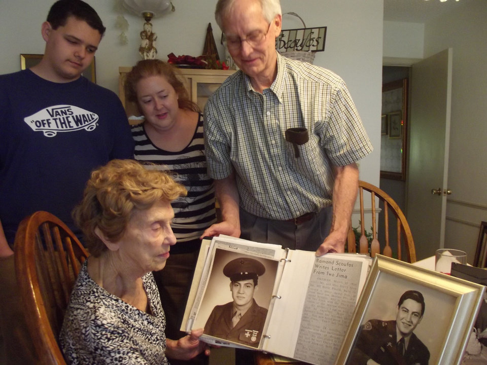 Photo - Billie Scoufos looks at photos of her late husband, Raymond Scoufos, surrounded by her great-grandson, Jared Lynch, her granddaughter Lezley Lynch and her son, Vince Scoufos.  Photo by Heather Warlick, The Oklahoman