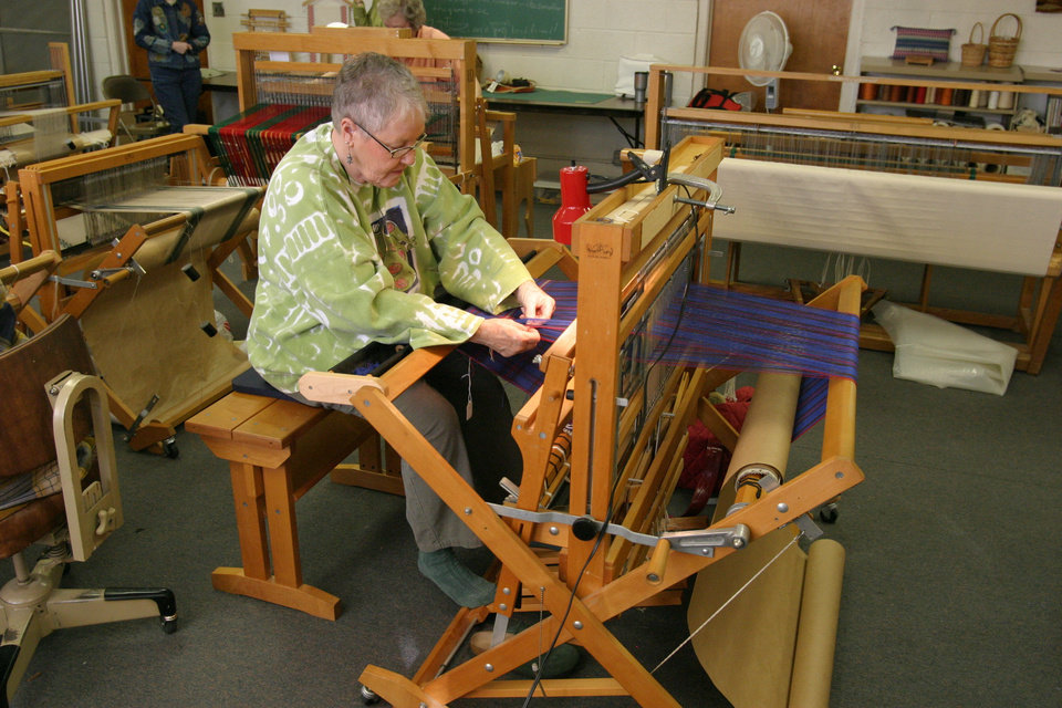 "Kathleen Oyler weaving tea towels in a family tartan pattern. A ""family tartan"" is a cloth woven with stripes of different colors and widths crossing at right angles with each ""family"" or clan having its own distinctive pattern Community Photo By: Bob Bozarth Submitted By: Sue, Guthrie"