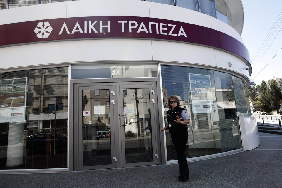 Photo - A private security guard gestures outside a Laiki bank branch in Nicosia, Cyprus, Thursday, March 28, 2013. Bank branches across the country were being replenished with cash, and are scheduled to open for six hours at noon (1000 GMT). Systems were frozen pending the official noon opening, and guards from a private security firm were reinforcing police outside some ATMs and banks in the capital, Nicosia. (AP Photo/Petros Giannakouris)