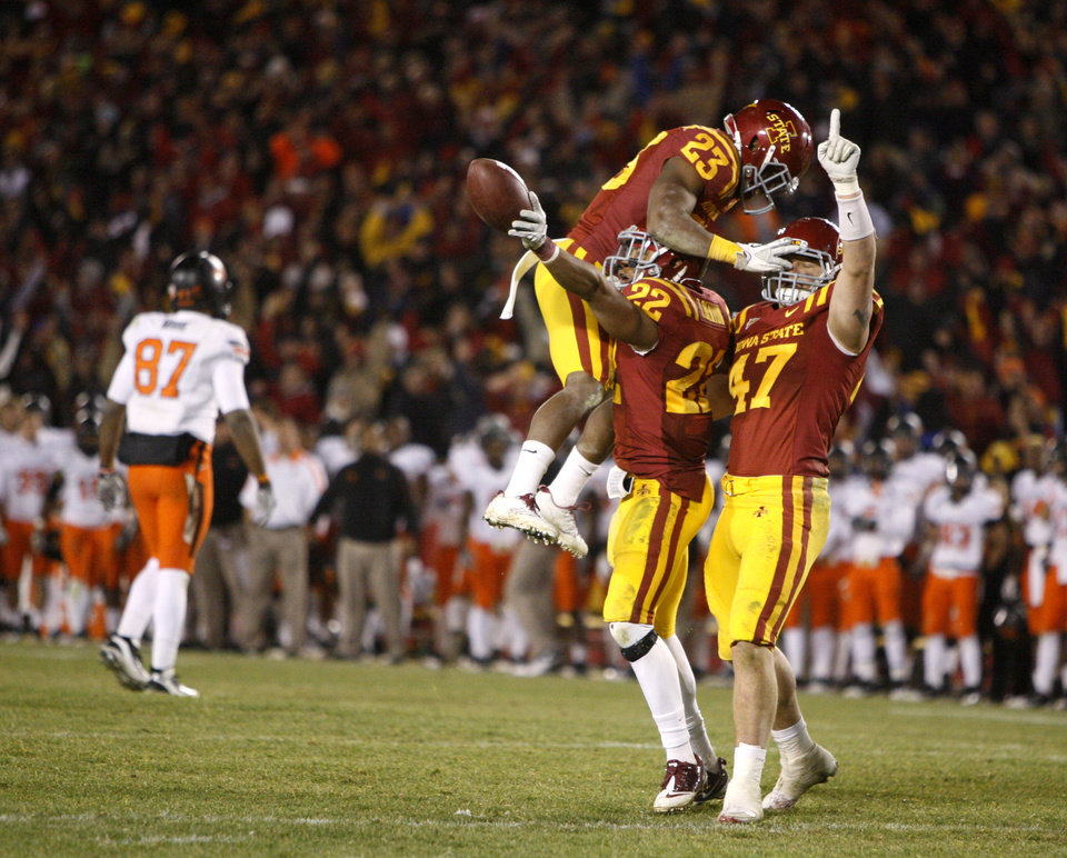 Photo - Iowa State's Leonard Johnson (23), Ter'Ran Benton (22), and A.J. Klein (47) celebrate after an interception in the second overtime of a college football game between the Oklahoma State University Cowboys (OSU) and the Iowa State University Cyclones (ISU) at Jack Trice Stadium in Ames, Iowa, Friday, Nov. 18, 2011. Photo by Bryan Terry, The Oklahoman