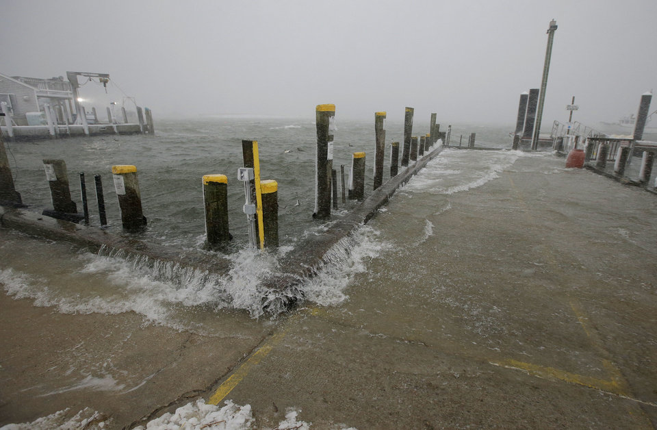 Photo - Sea water washes over the docks at the Chatham Fish Pier as high tide approaches in Chatham, Mass., Wednesday, March 26, 2014. A blizzard warning is in effect for Cape Cod, Martha's Vineyard and Nantucket as forecasters warned of wind gusts as high as 70 mph with near-zero visibility at times. (AP Photo/Stephan Savoia)