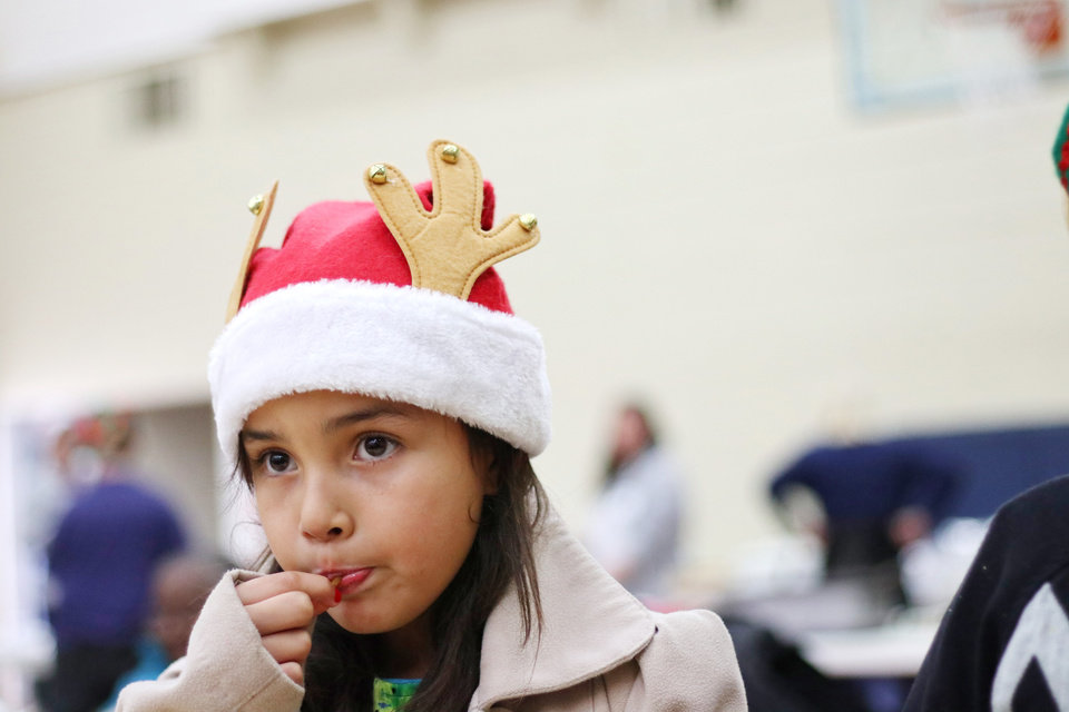 Photo - Nalania Alaska, 8, eats candy during the Christmas in the Hood party at the Oklahoma City Dream Center, Saturday, December 14, 2019. [Photo by Doug Hoke/The Oklahoman]