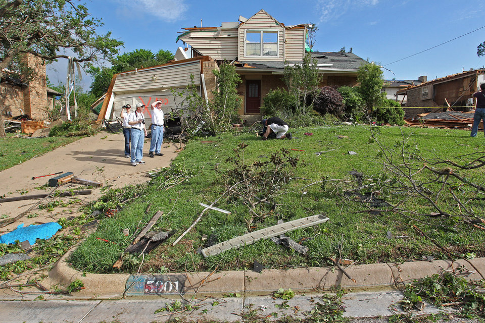 Mark Fox, right, of National Weather Service Warning & Coordination Meteorologist, and his staff look over the damage in the neighborhood after a severe storm passed the area, Wednesday, April 4, 2012 in Arlington, Texas. Preliminary findings indicate one of the tornadoes that struck North Texas had wind gusts ranging from 136 to 165 mph.  As many as a dozen twisters touched down across Dallas-Fort Worth. Thousands remained without power Wednesday and hundreds of homes were severely damaged.  Officials reported more than 20 injuries, but no deaths. (AP Photo/The Fort Worth Star-Telegram, Paul Moseley)  MANDATORY CREDIT ORG XMIT: TXFOR106
