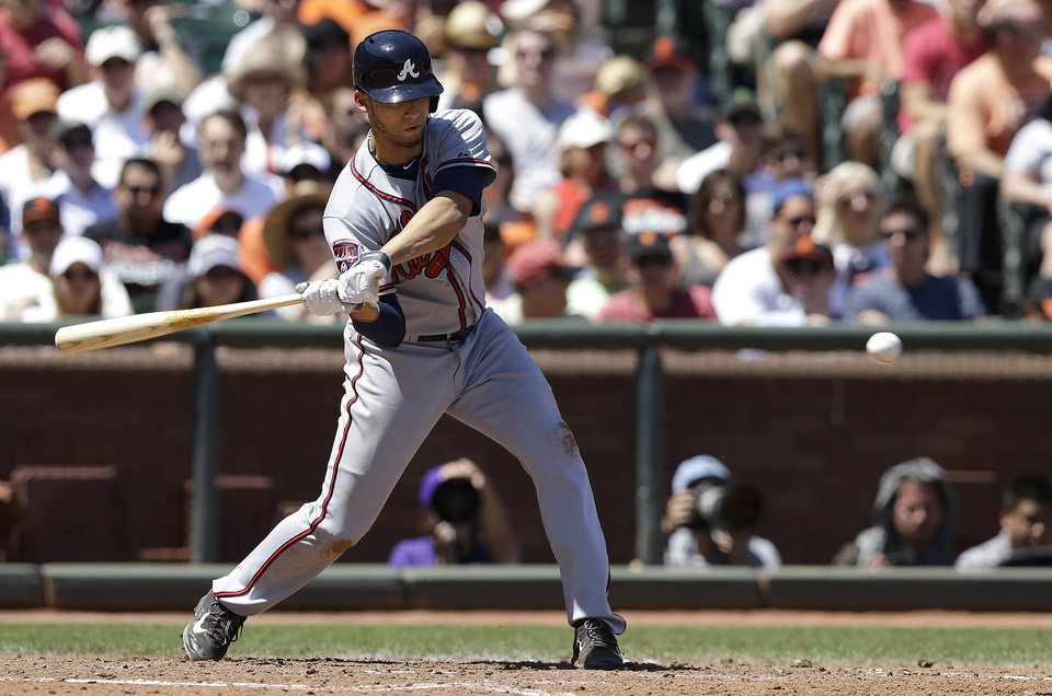 Photo - Atlanta Braves' Andrelton Simmons hits a triple off of San Francisco Giants pitcher Madison Bumgarner to score Chris Johnson during the fourth inning of a baseball game in San Francisco, Wednesday, May 14, 2014. (AP Photo)
