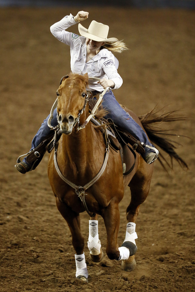 Photo - Megan Yurko of Wheeling, W.Va., celebrates her world championship in barrel racing at the end of her run during the International Finals Rodeo (IFR 44) at the Jim Norick Arena at State Fair Park in Oklahoma City, Sunday, Jan. 19, 2014. Photo by Nate Billings, The Oklahoman