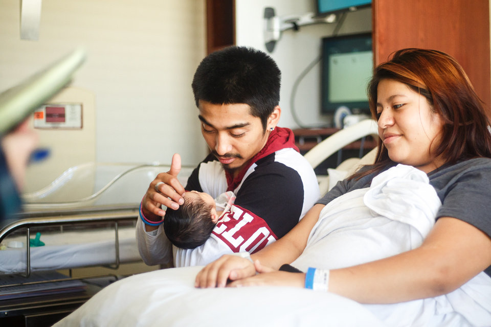 Photo - Joe Álvarez, 19, holds his newborn daughter Annayetzi while 17-year-old Leslie Marban rests on the bed at Mercy Hospital in Oklahoma City, Monday, July 16, 2018. Annayetzi was born early Saturday morning, July 14, 2018 weighing 6 pounds, 6 ounces. Photo by Anya Magnuson/The Oklahoman