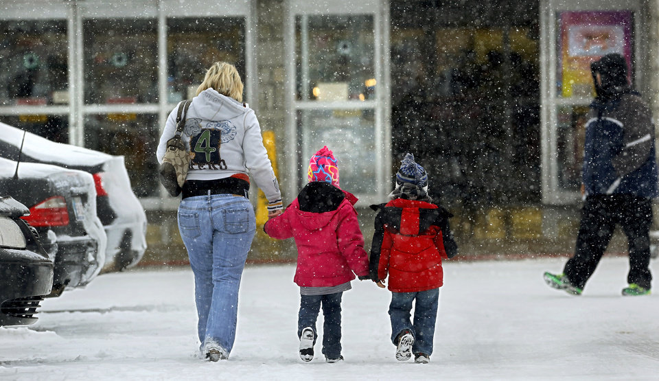 Photo - A woman walks with two small children into Crest Foods in Midwest City. Snow began falling in central Oklahoma around 7 Sunday morning, Feb. 2, 2014.   Photo by Jim Beckel, The Oklahoman