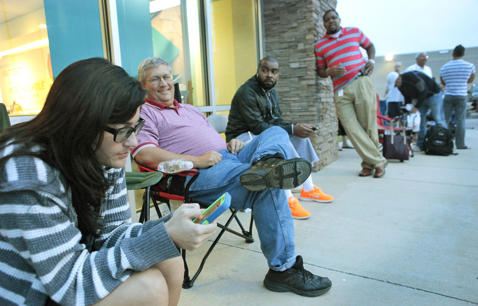 Photo - Niccole Rodenberger texts on her old iPhone while waiting in line for the new iPhones at the AT&T store on Memorial and Pennsylvania.  David McDaniel - The Oklahoman