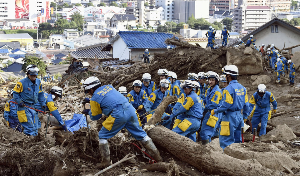 Photo - Police officers search for missing residents in a mud and rubble-covered residential area following a massive landslide in Hiroshima, western Japan, Thursday, Aug. 21, 2014.  Japanese police said rain-triggered landslides on the outskirts of Hiroshima city killed more than 30 people on Thursday with more than 50 people still missing, as search efforts continued in the devastated area. (AP Photo/Kyodo News) JAPAN OUT