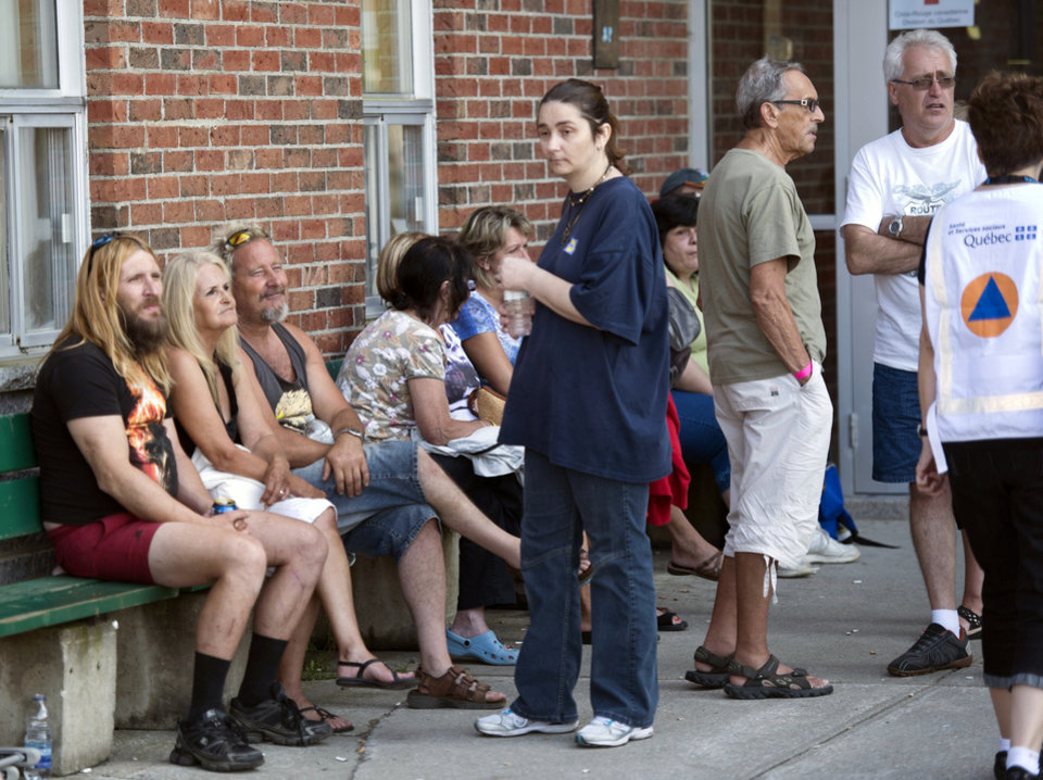 Photo - Residents wait outside an emergency center for news of family and friends following a train derailment in downtown Lac Megantic, Quebec, that caused explosions of railway cars carrying crude oil on Saturday, July 6, 2013. (AP Photo/The Canadian Press, Paul Chiasson)