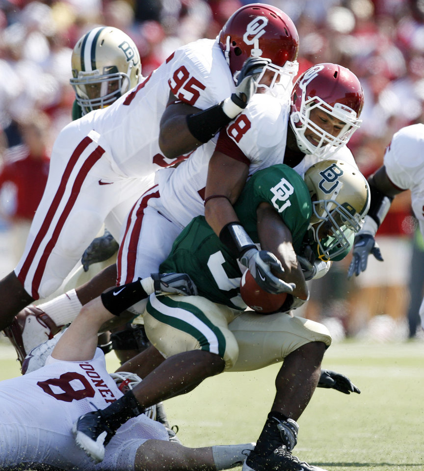 Photo - Jay Finley is brought down by Alan Davis (95) and Travis Lewis (28) in the first half during the college football game between Oklahoma (OU) and Baylor University at Floyd Casey Stadium in Waco, Texas, Saturday, October 4, 2008.   BY STEVE SISNEY, THE OKLAHOMAN