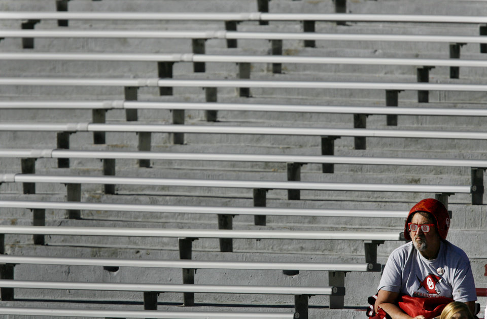 Photo - An Oklahoma fan sits in the stands before the start of the Bedlam college football game between the University of Oklahoma Sooners (OU) and the Oklahoma State University Cowboys (OSU) at the Gaylord Family-Oklahoma Memorial Stadium on Saturday, Nov. 28, 2009, in Norman, Okla.