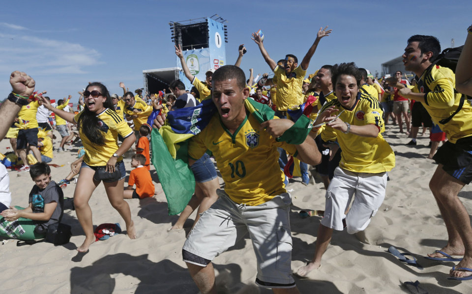 Photo - Colombia soccer fans celebrate their team's goal against Greece as they watch the World Cup game inside the FIFA Fan Fest area on Copacabana beach in Rio de Janeiro, Brazil, Saturday, June 14, 2014. (AP Photo/Silvia Izquierdo)
