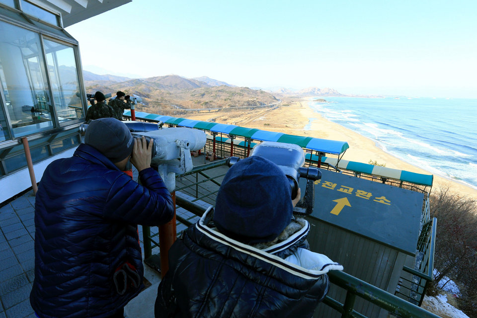 Photo - South Koreans use binoculars to look at Diamond Mountain in North Korea after news broke of North Korea's rocket launch at the Unification Observation post in Goseong, South Korea, Wednesday, Dec. 12, 2012.  North Korea successfully fired a long-range rocket on Wednesday, defying international warnings as the regime of Kim Jong Un took a big step forward in its quest to develop a nuclear missile. (AP Photo/Yonhap, Lee Jong-gun)   KOREA OUT ORG XMIT: SEL805