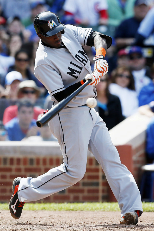 Photo - Miami Marlins' Adeiny Hechavarria hits an RBI-single against the Chicago Cubs during the seventh inning of a baseball game on Sunday, June 8, 2014, in Chicago. (AP Photo/Andrew A. Nelles)