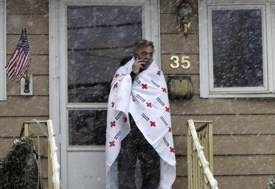 Ben Colontonio talks on his cell phone wrapped in a blanket donated by the American Red Cross as a Nor'easter approaches in the wake of Superstorm Sandy, Wednesday, Nov. 7, 2012, in Little Ferry, N.J. (AP Photo/Kathy Willens)