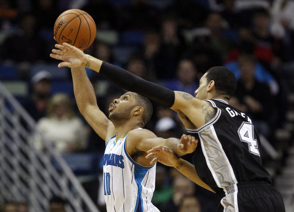 Photo - San Antonio Spurs guard Danny Green (4) reaches over New Orleans Hornets guard Eric Gordon (10) in the second half of an NBA basketball game  in New Orleans, Monday, Jan. 7, 2013. The Hornets defeated the Spurs 95-88.  (AP Photo/Bill Haber)
