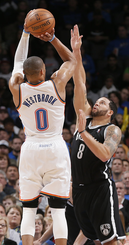 Photo - Oklahoma City's Russell Westbrook (0) shoots over Brooklyn Nets' Deron Williams (8) during the NBA basketball game between the Oklahoma City Thunder and the Brooklyn Nets at the Chesapeake Energy Arena on Wednesday, Jan. 2, 2013, in Oklahoma City, Okla. Photo by Chris Landsberger, The Oklahoman