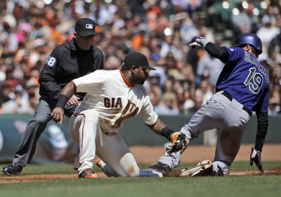 Photo - Colorado Rockies' Charlie Blackmon (19) steals third base next to San Francisco Giants third baseman Pablo Sandoval during the third inning of a baseball game on Saturday, April 12, 2014, in San Francisco. (AP Photo/Marcio Jose Sanchez)
