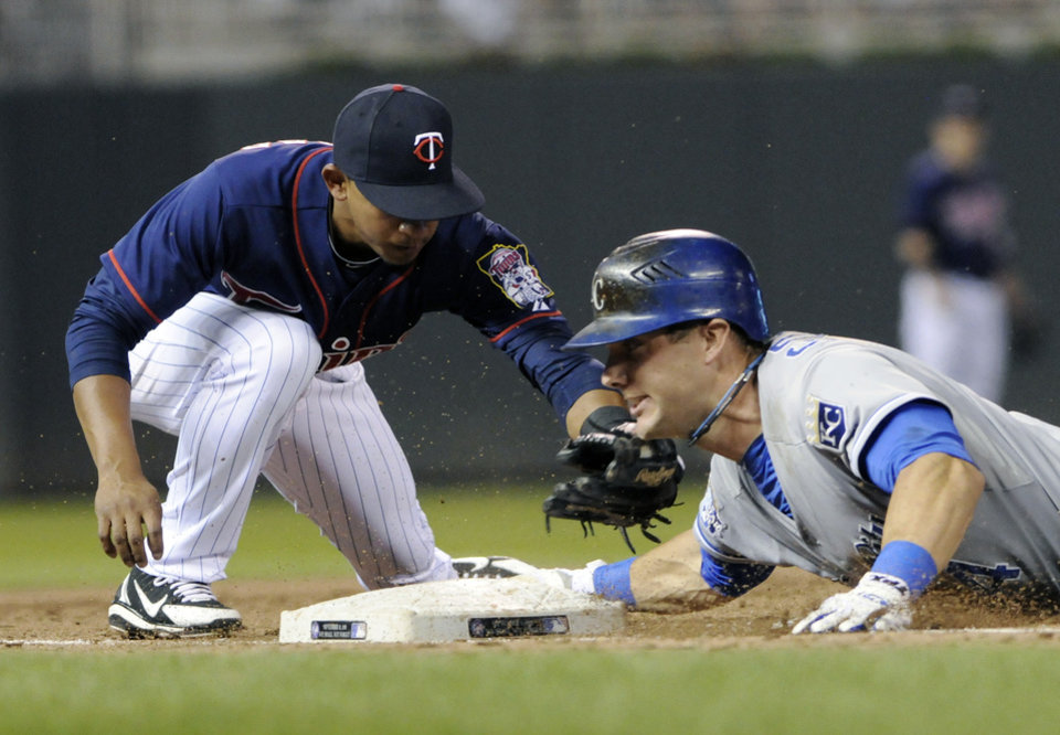Photo -   Kansas City Royals' Alex Gordon, right, beats the tag by Minnesota Twins third baseman Eduardo Escobar to triple off Twins' Scott Diamond in the third inning of a baseball game, Tuesday, Sept. 11, 2012, in Minneapolis. (AP Photo/Jim Mone)