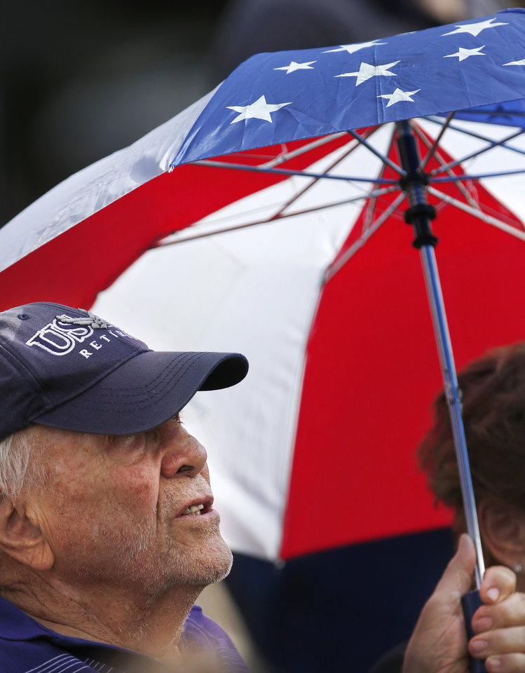 Photo - A man in the crowd shades his head with an umbrella during the 45th Infantry Division Museum's Memorial Day Ceremony on Monday, May 30, 2016. Photo by Jim Beckel, The Oklahoman